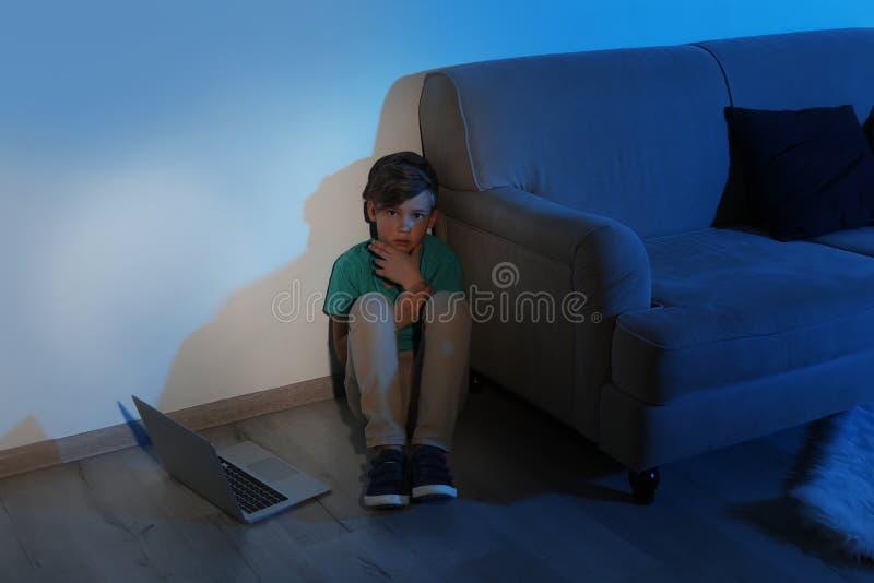 Petit enfant effrayé avec l'ordinateur portable sur le plancher Danger d'Internet images libres de droits