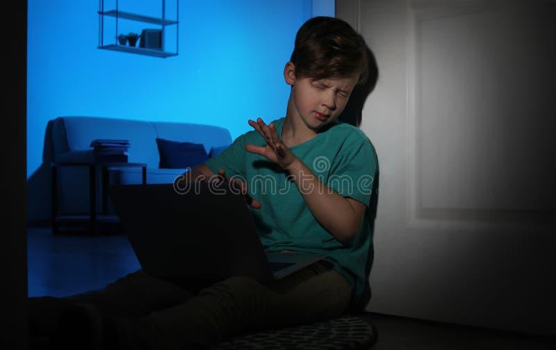 Petit enfant effrayé avec l'ordinateur portable sur le plancher dans la chambre noire image stock