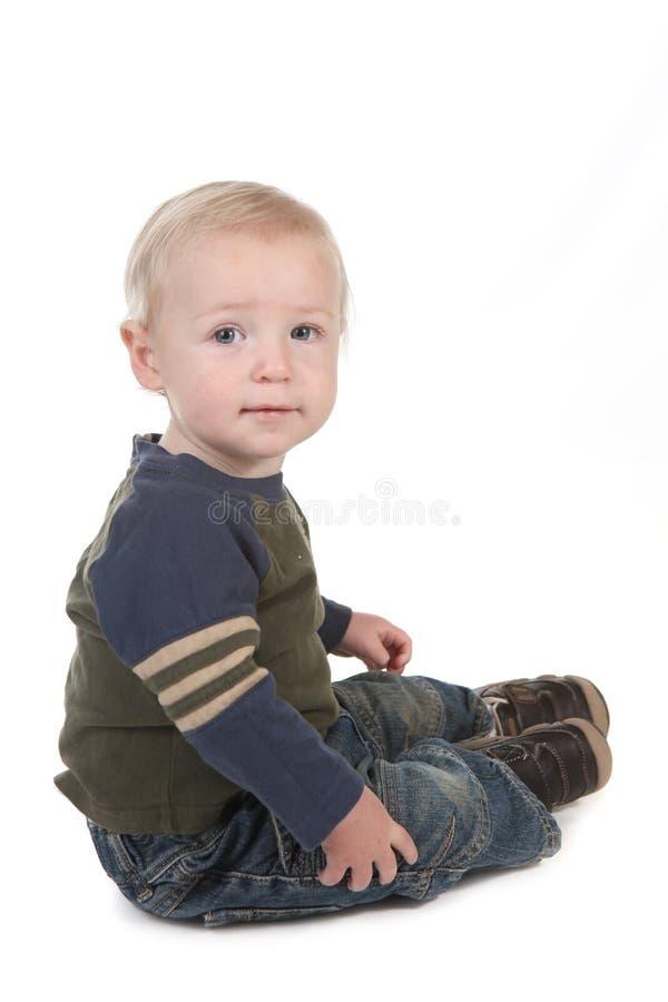 Petit enfant en bas âge de chéri s'asseyant de côté photo libre de droits