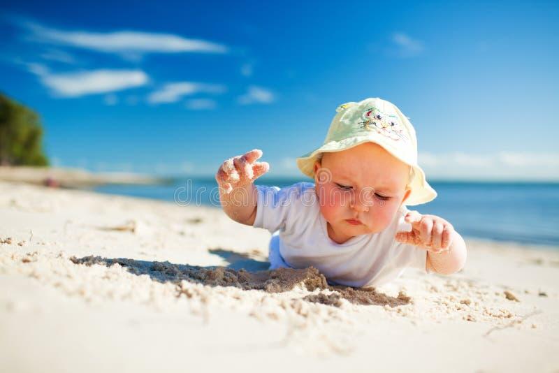 Petit enfant en bas âge sur le sable l'explorant de plage images libres de droits