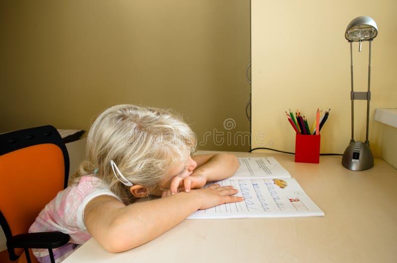 Petit enfant ennuyé et devoirs photos stock