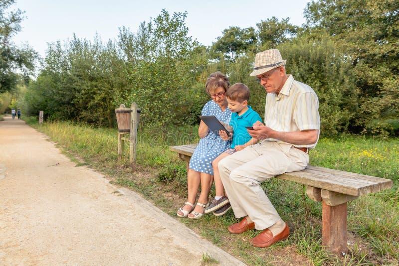 Petit-enfant et grand-mère à l'aide d'un comprimé dehors photos stock