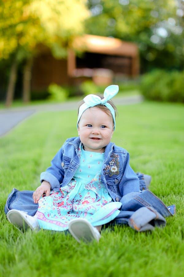 Petit enfant féminin heureux s'asseyant sur l'herbe verte et la veste de port de jeans photographie stock