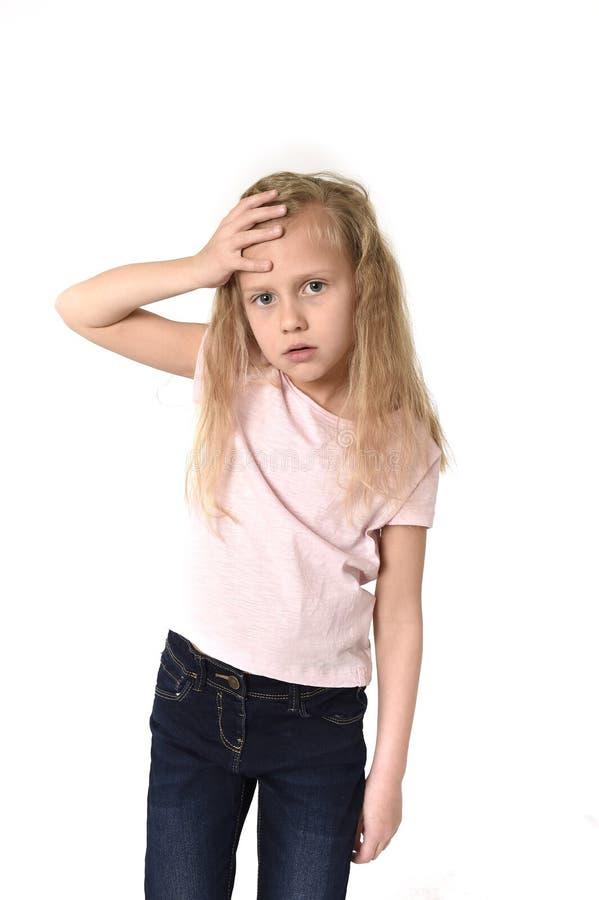 Petit enfant féminin mignon doux touchant son mal de tête de souffrance principal semblant fatigué et triste photographie stock libre de droits