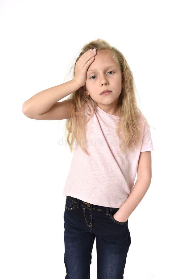 Petit enfant féminin mignon doux touchant son mal de tête de souffrance principal semblant fatigué et triste image libre de droits