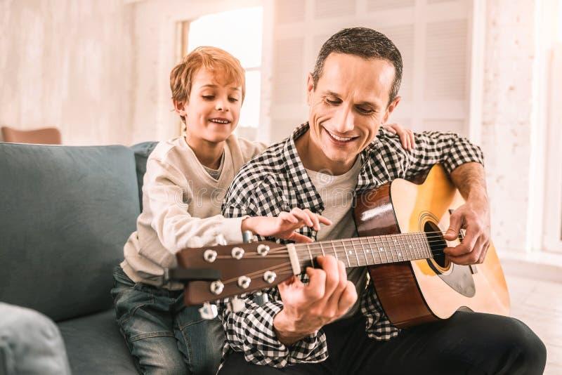 Petit enfant futé donnant à son papa un morceau de conseils musicaux images libres de droits