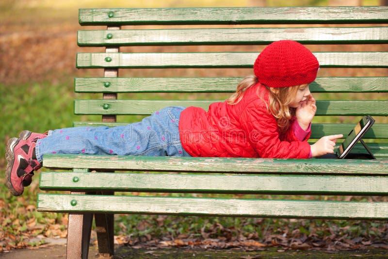 Petit enfant heureux travaillant avec le PC de comprimé photographie stock