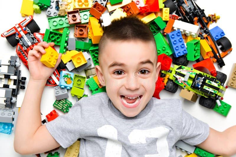 Petit enfant jouant avec un bon nombre de jouets en plastique colorés d'intérieur images stock