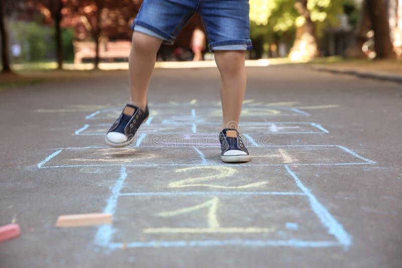 Petit enfant jouant le jeu de marelle dessiné avec la craie colorée photos libres de droits