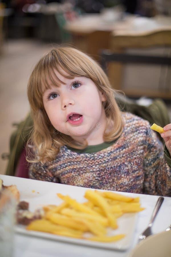 Petit enfant mangeant des pommes frites avec la main photo stock
