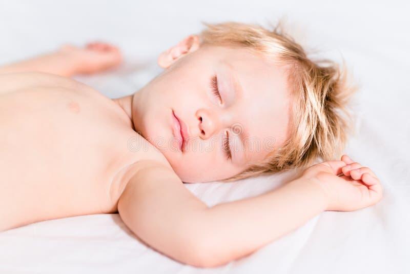 Petit enfant mignon avec les cheveux blonds dormant dessus sur le mauvais blanc photographie stock