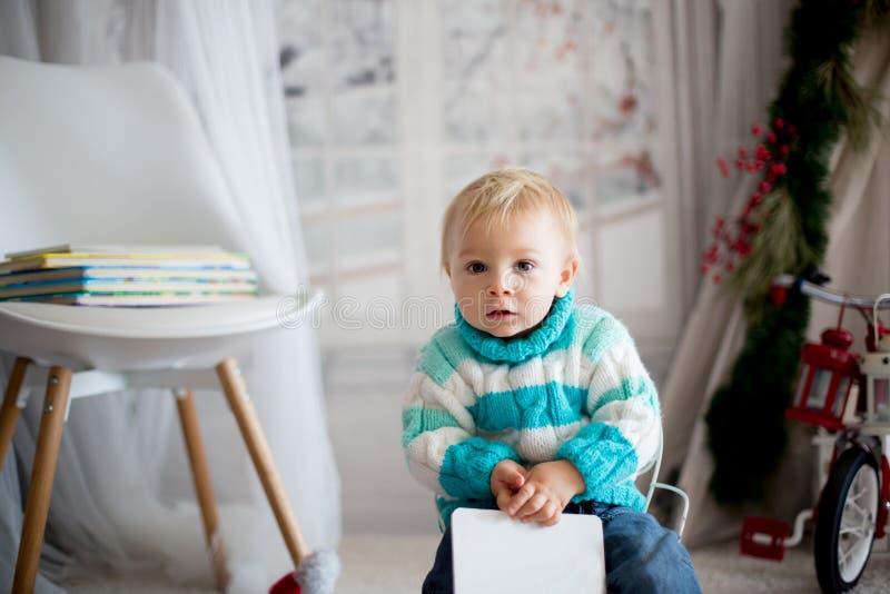 Petit enfant mignon d'enfant en bas âge avec le livre coloré à la maison un jour neigeux d'hiver photographie stock