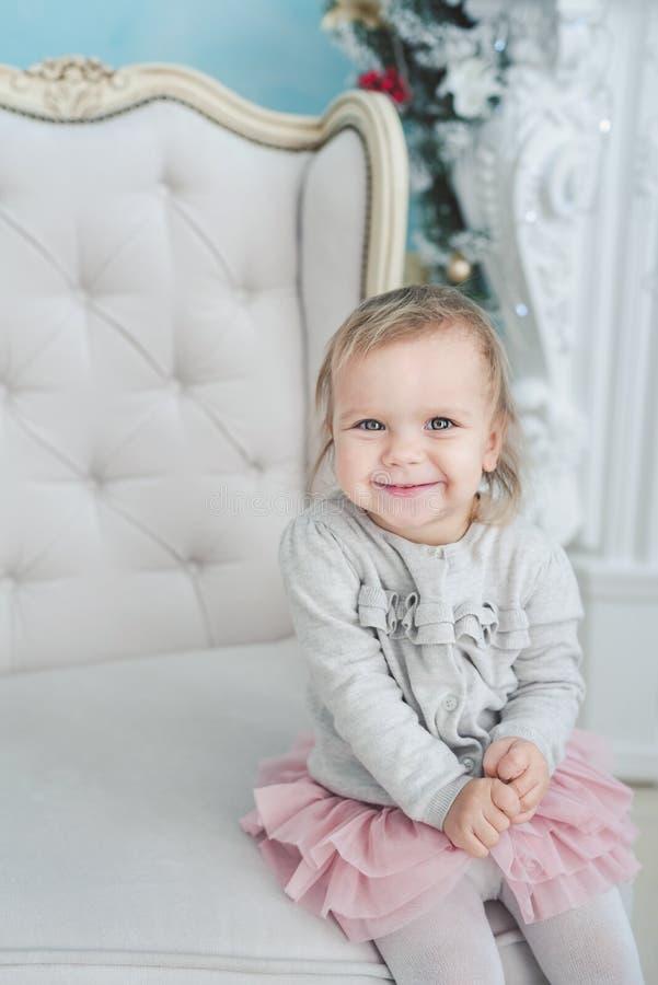 petit enfant mignon s'asseyant dans la chaise près de l'arbre de Noël An neuf heureux Petite fille de verticale Concept de No?l photo libre de droits
