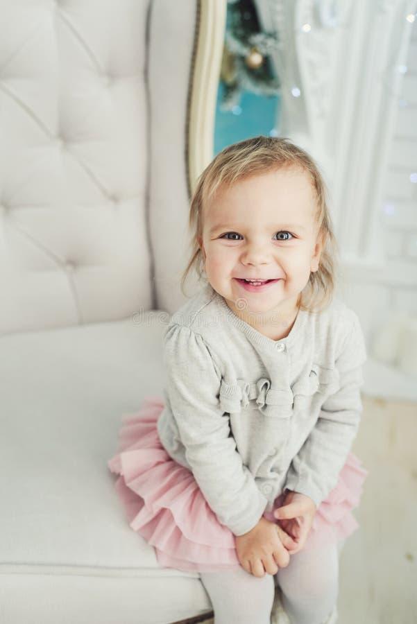 petit enfant mignon s'asseyant dans la chaise pr?s de l'arbre de No?l An neuf heureux Petite fille de verticale Concept de No?l photos stock