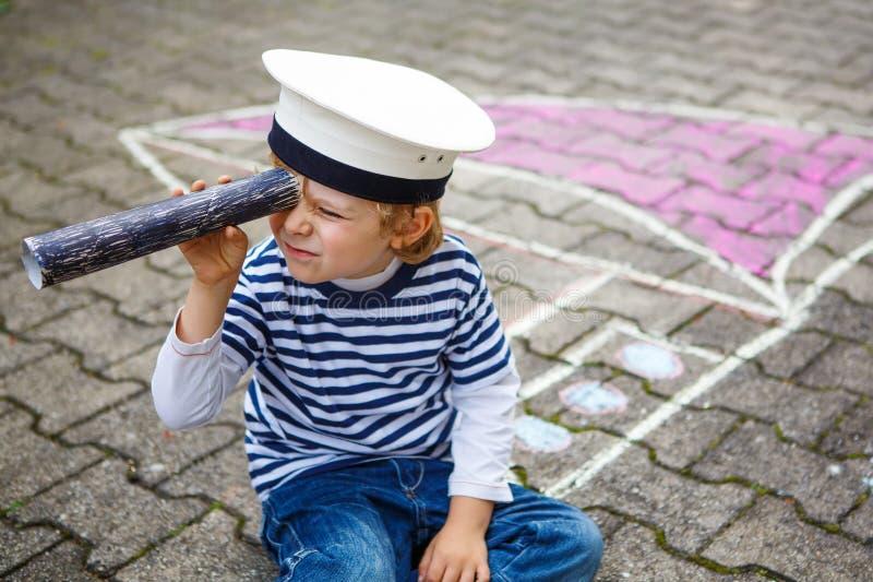 Petit enfant préscolaire ayant l'amusement avec le dessin de photo de bateau avec images stock