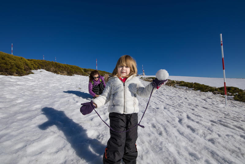 Petit enfant prêt à jeter la boule de neige photos stock