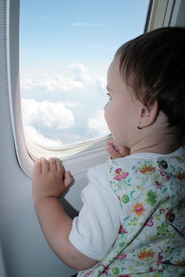 Petit enfant regardant par l'hublot de l'avion photos stock