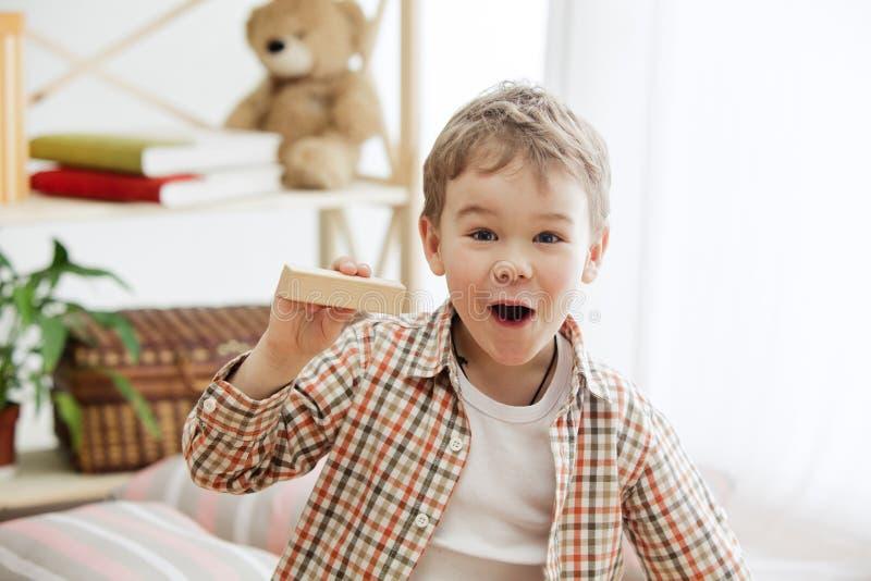 Petit enfant s'asseyant sur l'étage Joli garçon palying avec les cubes en bois à la maison photographie stock