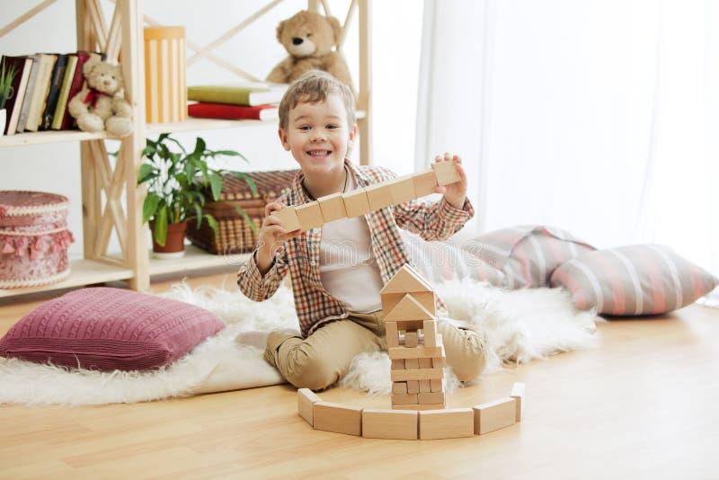 Petit enfant s'asseyant sur l'étage Joli garçon palying avec les cubes en bois à la maison image stock