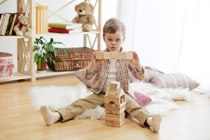 Petit enfant s'asseyant sur l'étage Joli garçon palying avec les cubes en bois à la maison image libre de droits