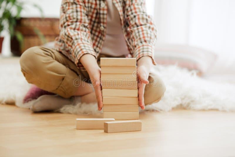 Petit enfant s'asseyant sur l'étage Joli garçon palying avec les cubes en bois à la maison images stock