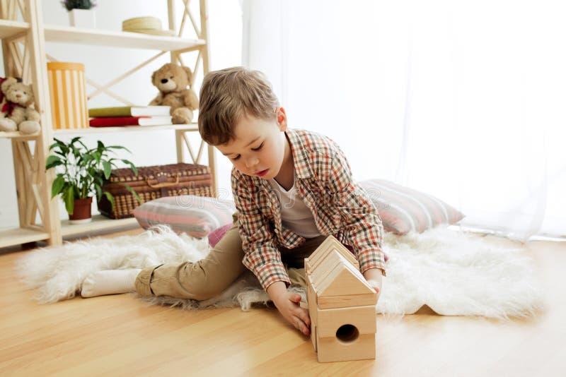 Petit enfant s'asseyant sur l'étage Joli garçon palying avec les cubes en bois à la maison photos libres de droits