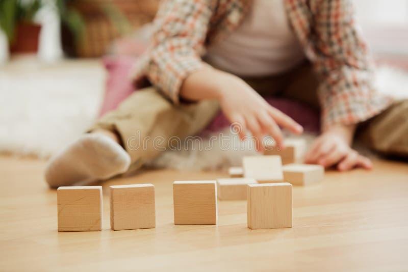 Petit enfant s'asseyant sur l'étage Joli garçon palying avec les cubes en bois à la maison photo libre de droits