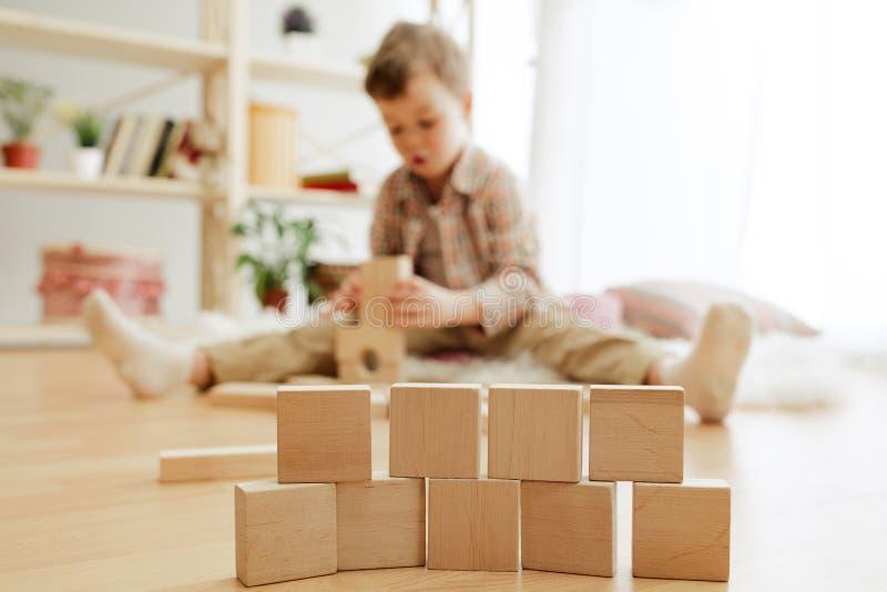 Petit enfant s'asseyant sur l'étage Joli garçon palying avec les cubes en bois à la maison images libres de droits