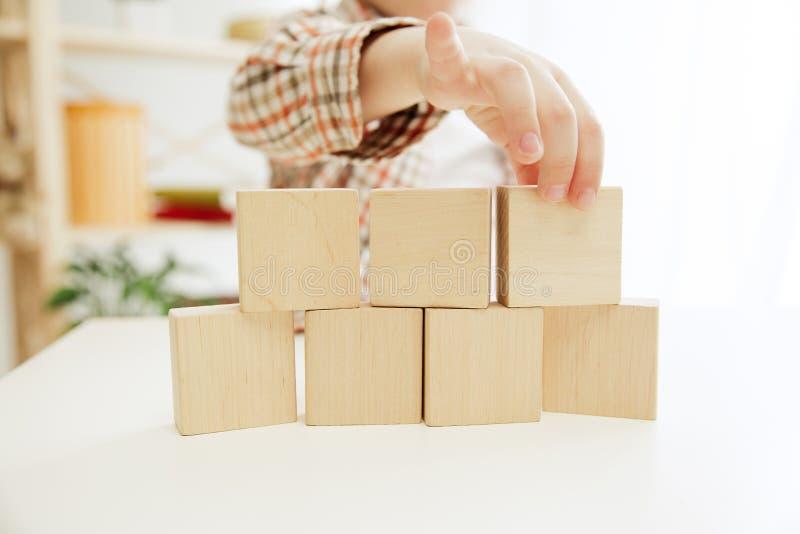 Petit enfant s'asseyant sur l'étage Joli garçon palying avec les cubes en bois à la maison photographie stock libre de droits