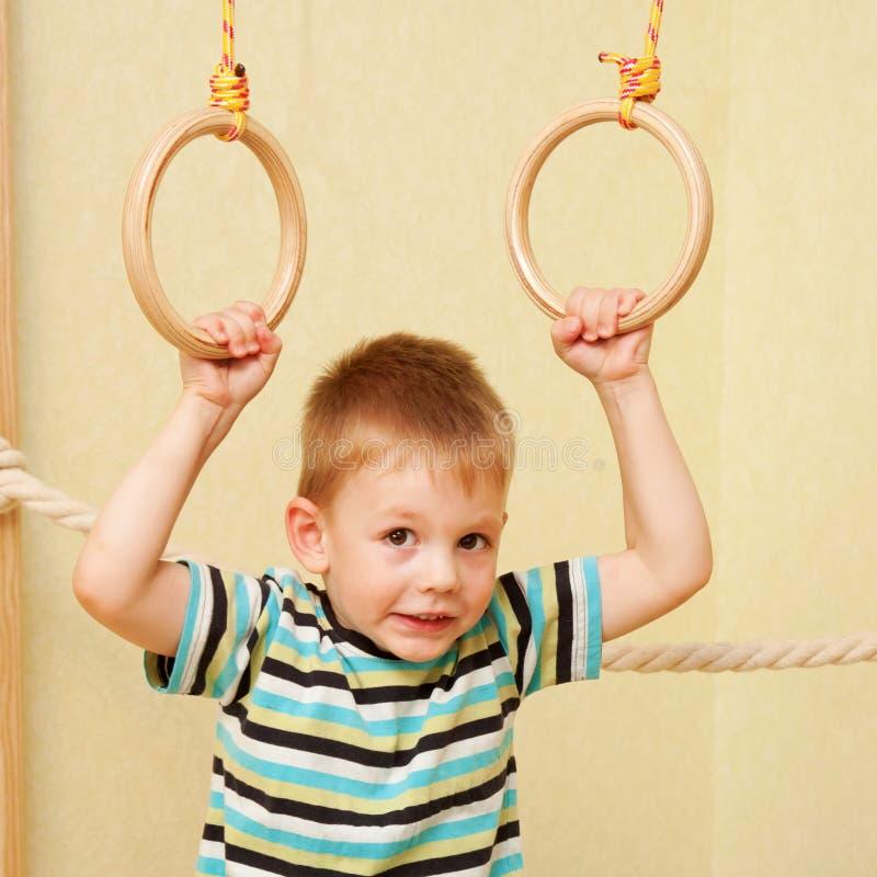 Petit enfant s'exerçant sur les anneaux gymnastiques photographie stock