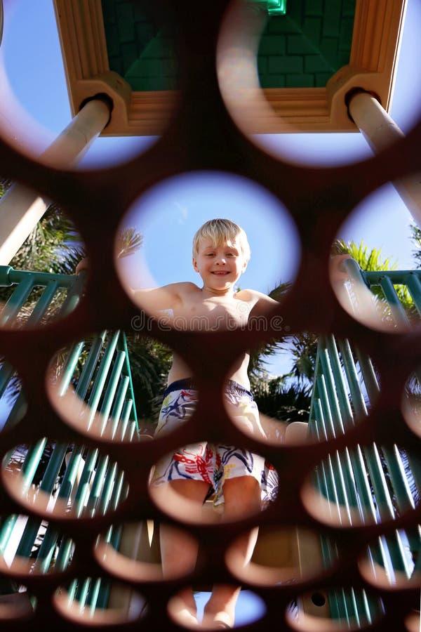 Petit enfant souriant tout en regardant par des cercles dans la plate-forme au terrain de jeu photographie stock