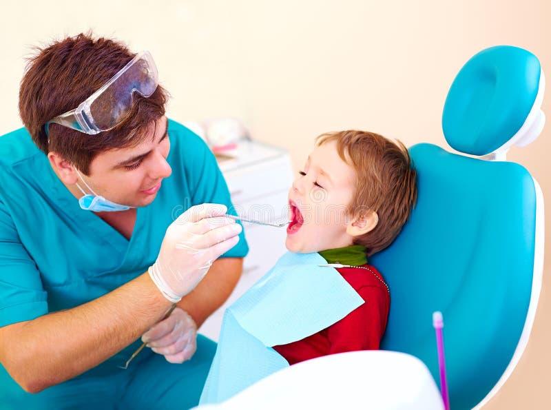 Petit enfant, spécialiste de visite patient dans la clinique dentaire images libres de droits