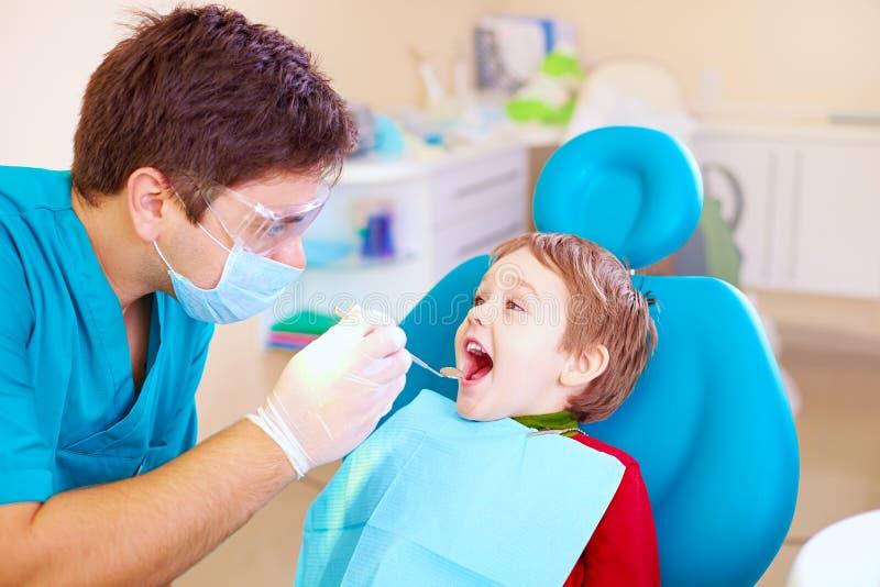Petit enfant, spécialiste de visite patient dans la clinique dentaire image libre de droits