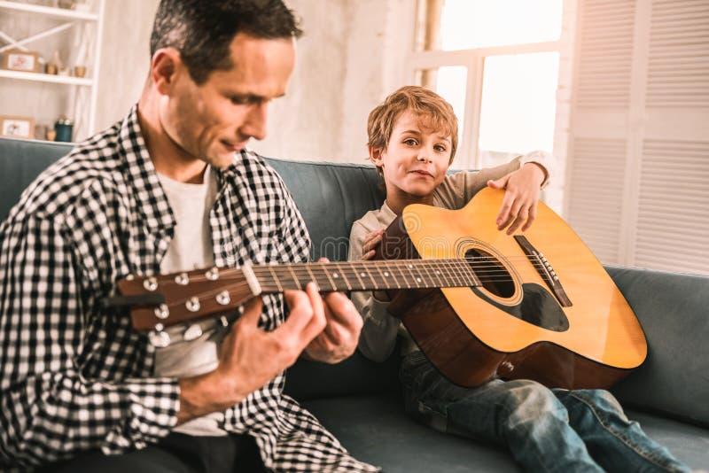 Petit enfant tenant une guitare rêvant de sa future carrière en tant que musicien images libres de droits