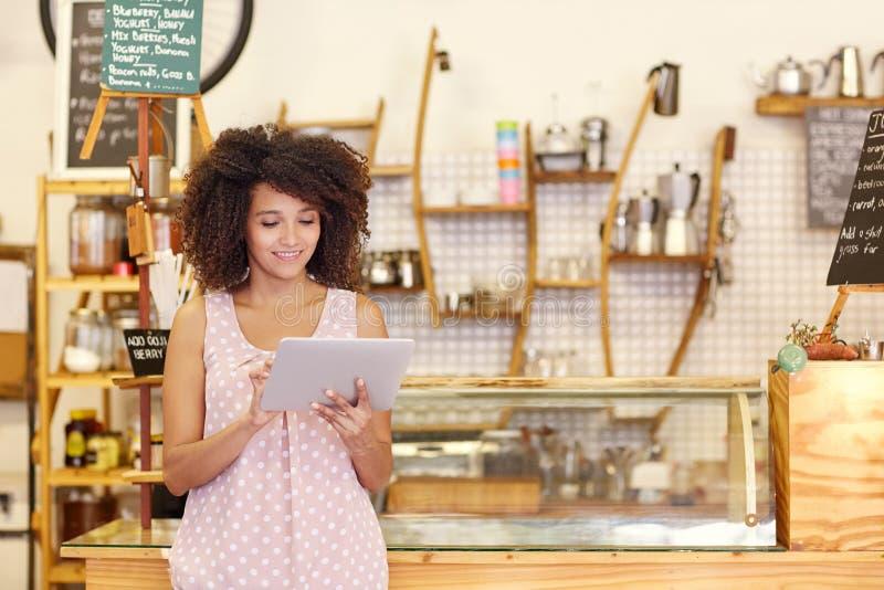 Petit entrepreneur à l'aide d'un comprimé dans son café images libres de droits