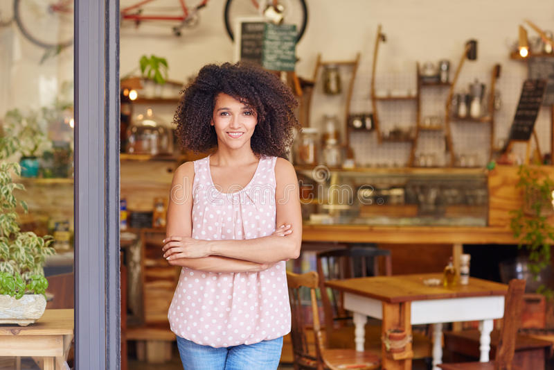 Petit entrepreneur se tenant dans la porte de son café image stock