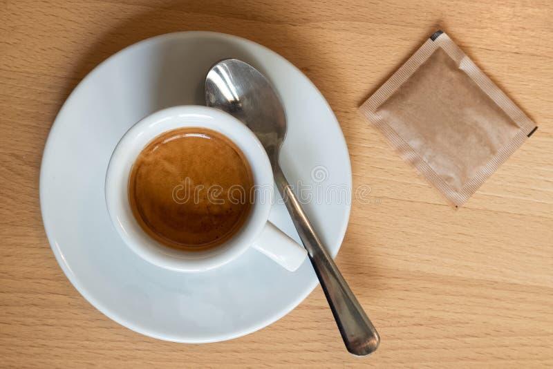 Petit expresso italien dans la tasse en céramique blanche avec la cuillère et le packe photos libres de droits