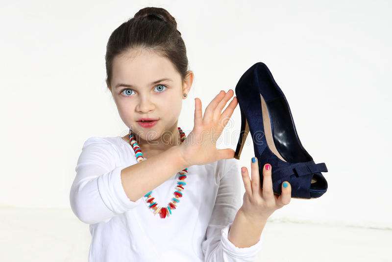 Petit fashionista retenant la chaussure photographie stock