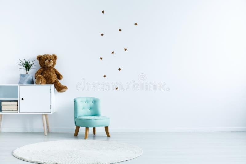 Petit fauteuil bleu-clair pour l'enfant se tenant dans l'interio de chambre blanche images libres de droits