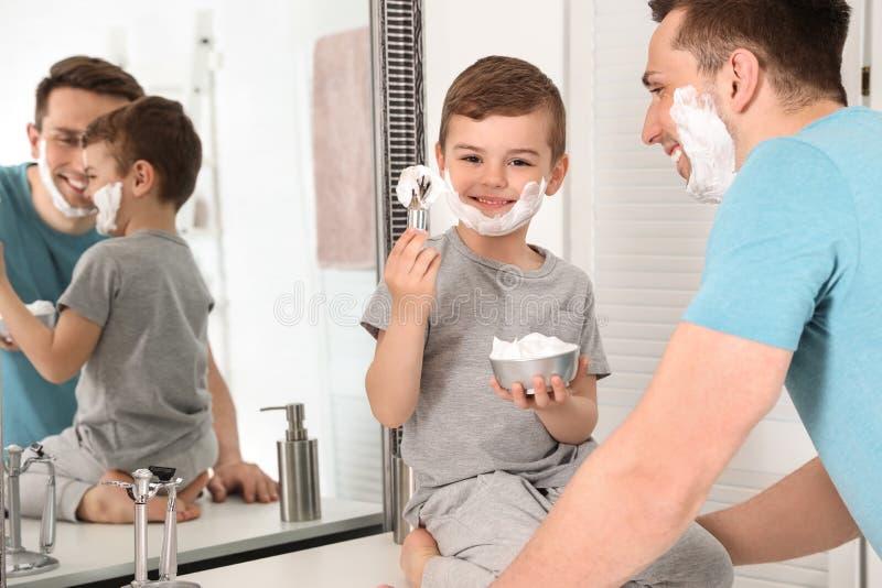 Petit fils avec la brosse de rasage et cuvette complètement de mousse près de papa images libres de droits