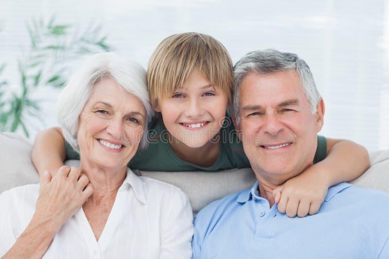 Petit-fils embrassant ses grands-parents image libre de droits