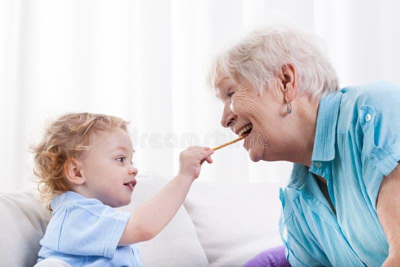 Petit-fils et grand-maman mangeant ensemble photos libres de droits