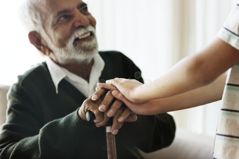 Petit-fils tenant des mains du ` s de grand-papa avec soin images libres de droits