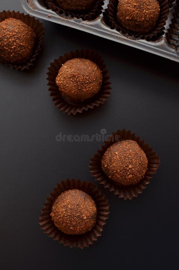 Petit fours för choklad över svart bakgrund Top beskådar arkivbild
