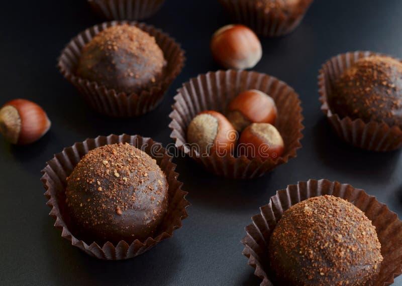 Petit fours för choklad med hasselnöten över svart bakgrund arkivbilder