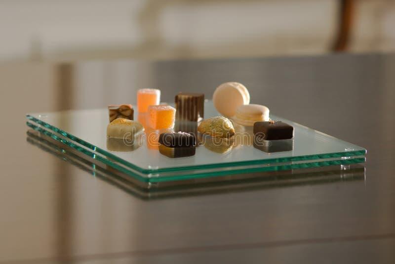Petit-fours op een moderne glasplaat stock foto
