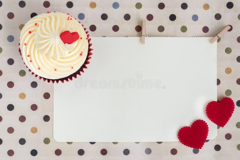 Petit gâteau avec deux coeurs rouges au-dessus de papier blanc image libre de droits