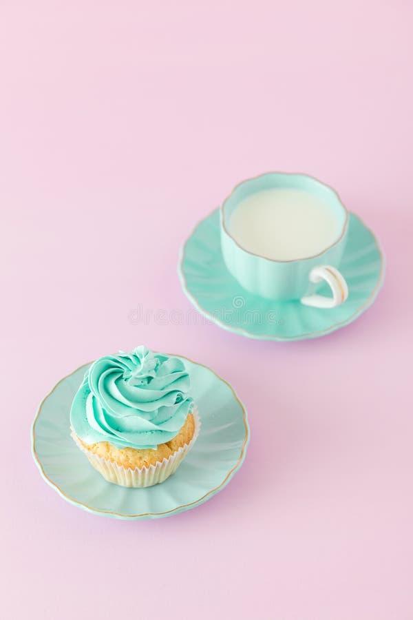 Petit gâteau avec la décoration et la tasse crèmes en bon état de lait et coffe sur le fond en pastel rose Carte de voeux de jour images libres de droits