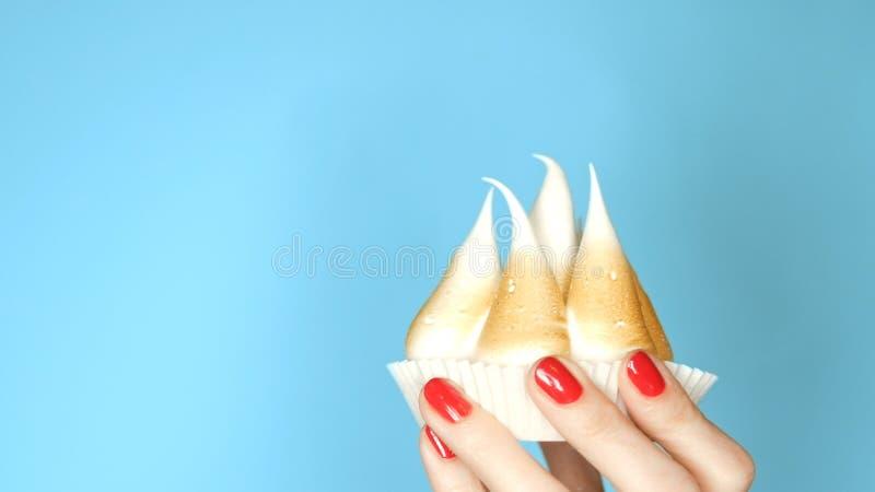 Petit gâteau avec la meringue dans une main femelle sur le fond bleu photos libres de droits
