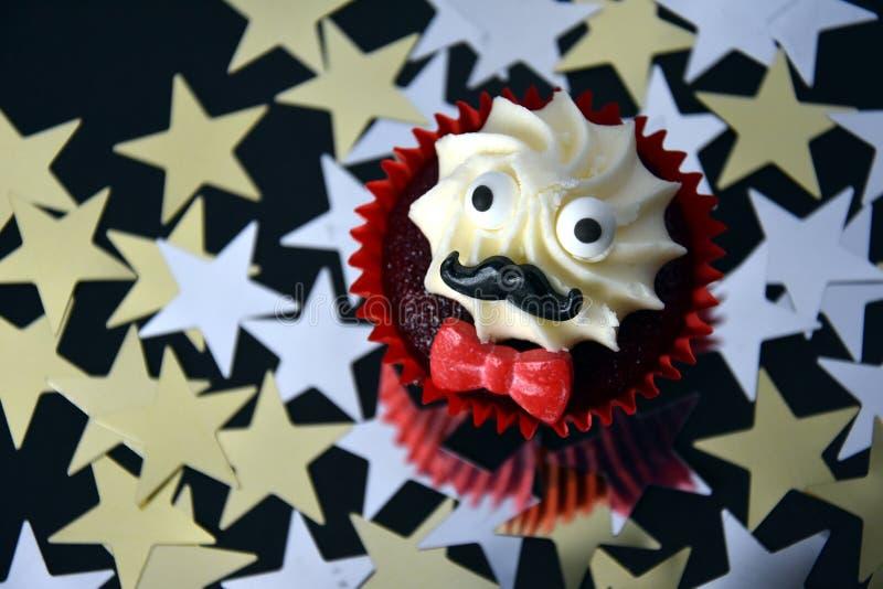 Petit gâteau avec la moustache noire, le noeud papillon rouge et la crème blanche sur le dessus images stock